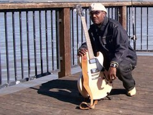 sam one holding guitar on peir